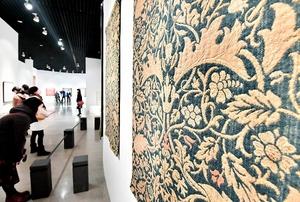 自然の草花や鳥をモチーフにした織物や壁紙に熱心に見入る来場者=25日、福井市美術館