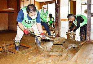 家屋内の泥かきをするボランティア参加者=7月12日、京都府舞鶴市