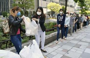コメや野菜を受け取るため、JR名古屋駅前に集まったベトナム人ら=30日午前