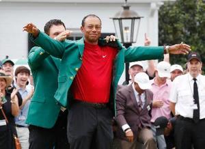 2005年以来5度目の大会制覇を果たし、グリーンジャケットの袖に手を通すタイガー・ウッズ=オーガスタ・ナショナルGC(共同)