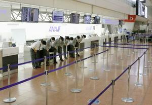 新型コロナウイルスの影響で閉鎖していた搭乗カウンターが再開され、一礼する全日空のスタッフ=7月、羽田空港