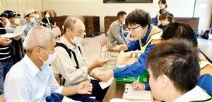 原子力防災訓練で福井県おおい町の職員らからヨウ素剤に見立てたあめ玉をもらう町民=8月26日、同町ふるさと交流センター