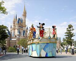 7月の営業再開を前に報道公開された東京ディズニーランド。パレードに代わり、台車に乗って園内を回るミッキーマウスら=6月29日、千葉県浦安市