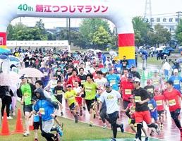降りしきる雨の中、勢いよくスタートする2キロ親子の部のランナー=5月13日、福井県鯖江市東公園陸上競技場
