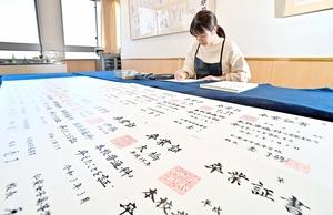 一枚一枚、丁寧に名前が書き込まれる卒業証書=1月25日、福井県福井市の仁愛女子高校