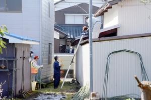 クマが入り込んだとみられる車庫(右)の周辺で警戒に当たる猟友会員ら=10月29日午前9時45分ごろ、福井県福井市稲津町