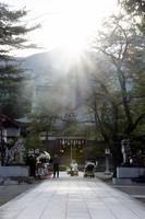 篠座神社拝殿の背後にある飯降山の山頂に夕日が沈み、夕日、山頂、拝殿、参道が一直線上になった光景=9月23日、福井県大野市篠座の篠座神社