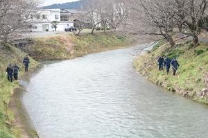 吉野瀬川沿いを捜索する警察官=10日、福井県越前市上太田町
