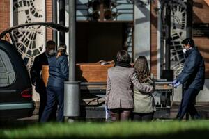スペインの首都マドリードで、新型コロナウイルスによる犠牲者のひつぎを見つめる親族=28日(AP=共同)