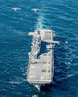 米海軍の強襲揚陸艦「アメリカ」と共同訓練する空自のF35Aステルス戦闘機2機(左上)=20日(航空自衛隊提供)