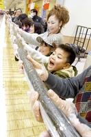 参加者が息を合わせて完成させた全長約100メートルの巻きずし=2月3日、福井県大野市のヴィオ