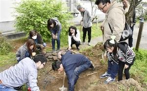 タイムカプセルを見つけようと、土や石を掘り起こす卒業生ら=福井県福井市明新小学校