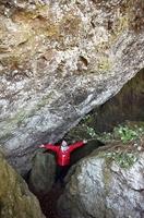 上部を覆うような岩の形状が伝記中の「坂本の岩屋」に似ているとして、内部の調査を進める堀大介学芸員=福井県越前町小川