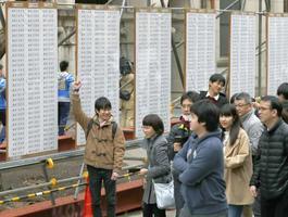 東大の前期日程入試の合格発表で、掲示板の前でガッツポーズする受験生=10日午後、東京都文京区