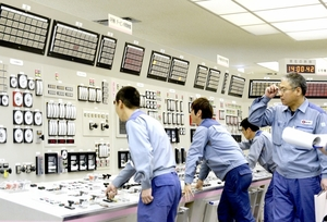 計器を見ながら、発送電開始のスイッチを入れる運転員=22日、福井県高浜町田ノ浦の高浜原発(代表撮影)