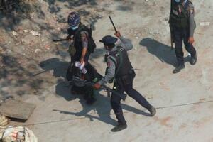 6日、ミャンマー最大都市ヤンゴン郊外でデモ参加者を制圧する治安当局者ら(AP=共同)