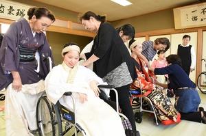 車椅子利用者に白無垢を着付ける三田村さん(左)ら=福井県越前市文化センター