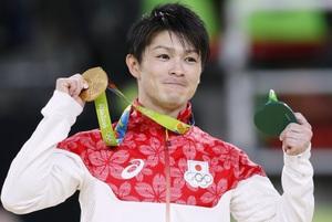 男子個人総合で獲得した金メダルを手に笑顔の内村航平=リオデジャネイロ
