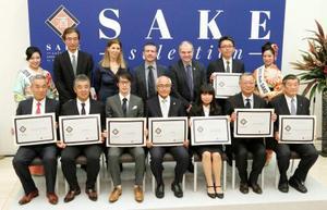 サケ・セレクションの各部門でトロフィー酒に選ばれ、記念撮影する日本酒の作り手ら=21日午後、東京都千代田区のベルギー大使館