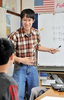 生徒に数学を教える石田益資。笑顔を絶やさないよう心掛けている=3月、福井市松本3丁目のみんなの広場