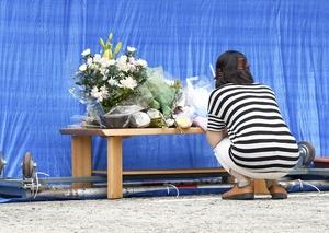火災が起きた豊島繊維の事務所前に設けられた献花台の前で手を合わせる女性=6月23日午後1時20分ごろ、福井県永平寺町
