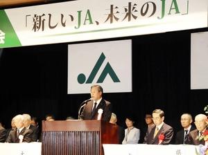 福井県1JAの合併基本構想を決議したJA県大会であいさつする田波俊明会長(中央)=11月27日、福井市の県農業会館