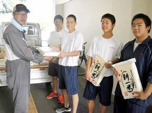 真空パックのコシヒカリを運動部の部員に渡す池田さん(左)=敦賀市の敦賀高