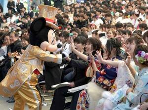 東京ディズニーランドで開かれた千葉県浦安市の成人式でミッキーマウスの祝福を受ける新成人=13日