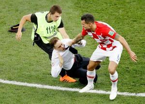 フランス―クロアチア 後半、ピッチへの乱入者を引きずり倒すクロアチアのロブレン(右)=モスクワ(共同)