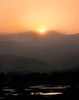 白山の御前峰(中央右)と大汝峰(同左)の間から昇る朝日=8日午前5時22分、福井県勝山市鹿谷町保田から松村透さん撮影