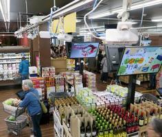 店舗の天井近くに設置されたAIカメラと連動してお客に商品を提案する液晶画面=19日、福岡県新宮町