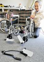 三宅勇三さんが開発した「ラクアップレバー」(手前)。既製の車いすに装着でき、手元のレバー操作でフットプレートが開閉する=福井県小浜市