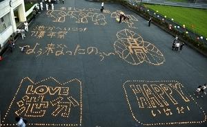 武生高校池田分校の校章などが浮かび上がった4千個のキャンドルアート=8月17日、福井県池田町の同分校