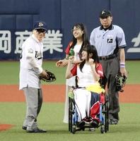 始球式に臨む牧野百男市長(左)にボールを渡した後、車いすから声援を送る猪狩ともかさん=8月31日、大阪府大阪市の京セラドーム大阪
