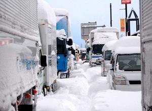 国道8号で雪に埋まったトラックや乗用車。最大で約1500台が立ち往生した=2018年2月6日、福井県坂井市丸岡町一本田中