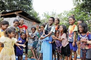 蛇口から出る水に笑顔を見せるウラホー村の子どもたち=9月、東ティモール(福井県大野市提供)