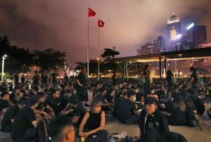 「逃亡犯条例」改正案の撤回を求め、立法会近くで座り込む人たち=16日、香港(共同)