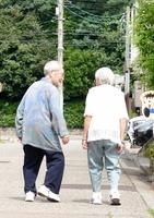 2人で散歩する磯野信雄さん(左)とチヨ子さん。「たくさんの人に支えられて今がある」と話す=7月、福井県福井市内