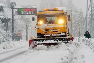 今冬初めて出動し、雪が降り続く中で作業に当たる除雪車=27日午前10時半ごろ、福井県勝山市北谷町谷の国道157号