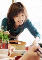 訪れた高齢者たちに笑顔で食事を提供する早川緑さん=4月17日、福井県福井市の「まちよかcafe」