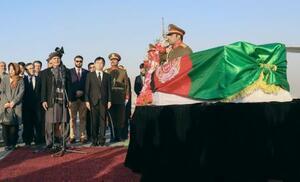 アフガニスタン国旗に包まれた中村哲さんのひつぎとマイクの前でスピーチするガニ大統領=7日、カブール(共同)