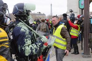 12日、パリの凱旋門前で警戒する警官と、黄色いベスト運動のデモ参加者ら(共同)