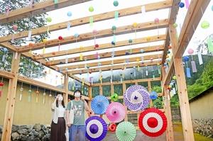 復原町並の「和傘スカイ」を楽しむカップル=7月23日、福井県福井市の一乗谷朝倉氏遺跡