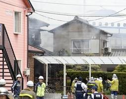火災があった愛知県清須市の住宅(左奥)。右奥は運転が再開され、現場近くを通過する東海道新幹線=3日午後0時21分