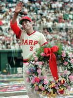 1987年6月、試合終了後、連続試合出場世界新達成で「2131」を記した花輪を手に観客の祝福に応える衣笠祥雄選手=広島