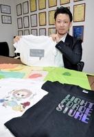 光を当てると、反射材で描かれたメッセージが浮かぶTシャツを手にする雨森研悟専務=2月12日、福井県福井市の丸仁
