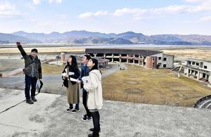 旧大川小学校の裏山に登り、弟を亡くした永沼悠斗さん(左端)の話を聞く福井高専の3人=2月26日、宮城県石巻市