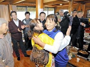 福井県内の支援者と抱き合い、別れを惜しむ川崎さん(中央右)=28日、福井県坂井市