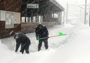 線路の除雪をする駅員=6日午前、福井市の福井鉄道田原町駅