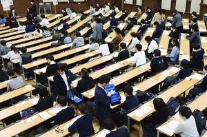 機器の配布を待ち、リスニングの試験に臨む受験生=2019年1月19日午後、東京都文京区の東京大学(代表撮影)